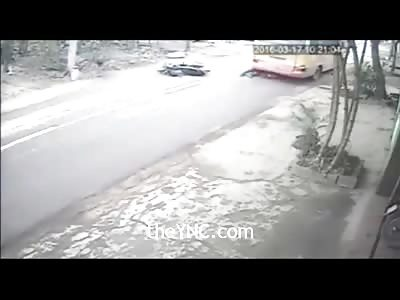 Biker Slides Under Bus Wheel