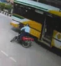 SQUISH: Motorcyclist Falls Under Bus