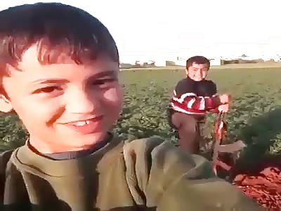 Iraqi boy shooting an AK47.