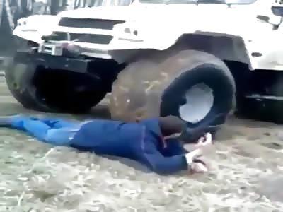 crazy man lets a big bear 4x4 four wheeler run over him