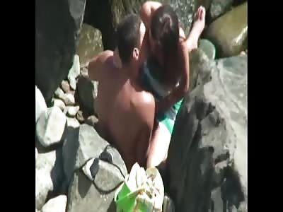 Couple Filmed on Beach Through Scope