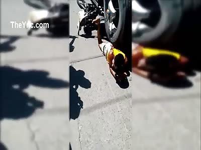 Motorcyclist stuck under wheels of Truck.